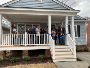 Ms. Harris and two of her children celebrate their accomplishment on the front porch of their new blue, single-story home.