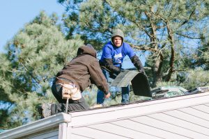 Two men remove and replace shingles on a one-story home.