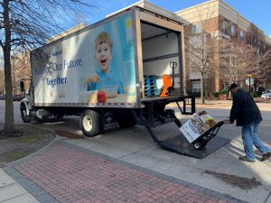 Virginia Peninsula Foodbank staff member loads the truck with a box of collected donations.